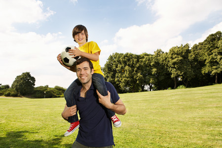 Father carrying son on shoulders with football