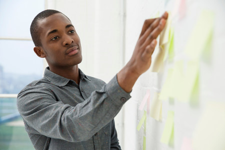 afro caribbean ethnicity: Young man sticking adhesive notes to wall