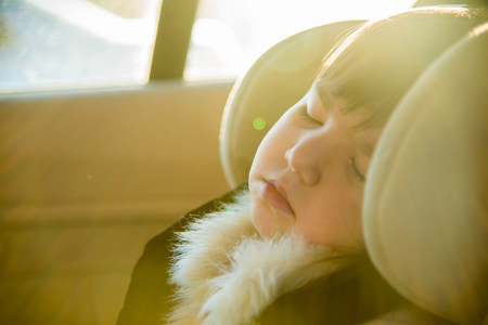 go inside: Close up of young girl sleeping in car LANG_EVOIMAGES