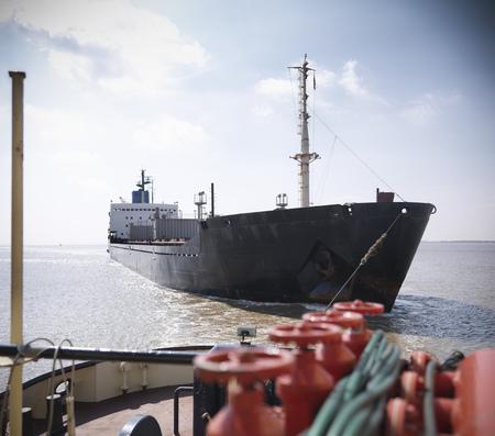 towed: Tugboat pulling ship in ocean LANG_EVOIMAGES