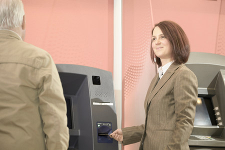 two persons only: Woman using cashpoint,man waiting