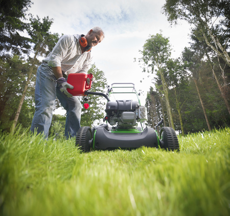 defended: Man pouring gas into lawn mower