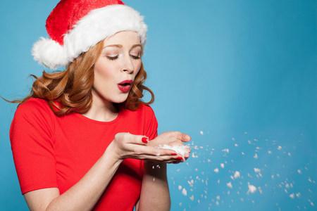 Woman wearing santa hat blowing snow