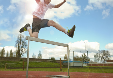 Boy jumping over hurdle on track