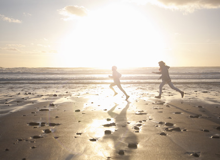 pursued: Mother and son running on beach LANG_EVOIMAGES