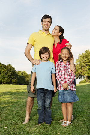 cheer full: Portrait of family with two children standing on grass