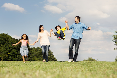 Family with two children,parents swinging boy