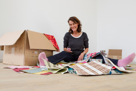 wooden floors: Woman sitting on floor with box of fabric samples