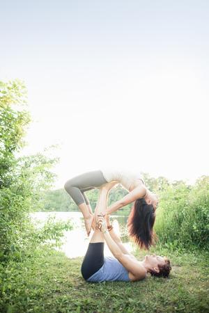 faiths: Couple practicing yoga in garden