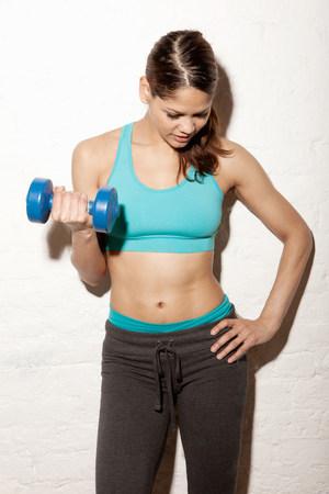 levantar peso: Mujer joven con el peso de la mano LANG_EVOIMAGES