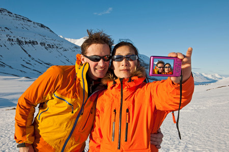 Mature couple taking self portrait in snow covered mountains,Skidadalur,Dalvik,Iceland