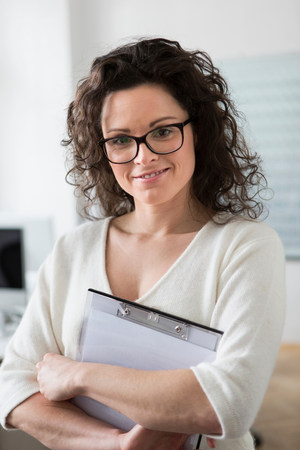 35 to 40 year olds: Portrait of woman holding clipboard