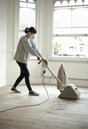 Mature woman sanding floor of new home
