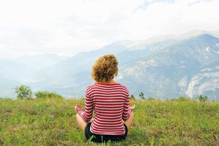 mountainous: Woman meditating on rural hilltop LANG_EVOIMAGES