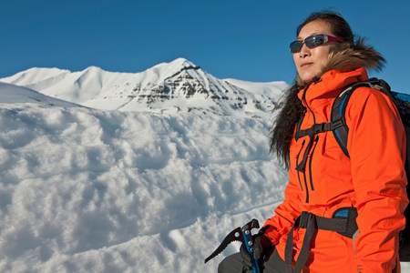 winter escape: Mature woman hiking in snowy mountains,Skidadalur,Dalvik,Iceland LANG_EVOIMAGES
