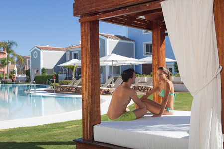 honeymooner: Young couple sitting on sunlounger at holiday resort