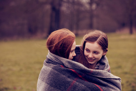 Girls wrapped in a blanket outdoors,smiling