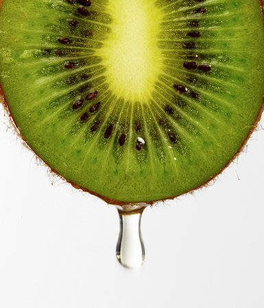 actinidia deliciosa: Juice dripping from kiwi LANG_EVOIMAGES