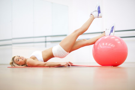 Young woman in gym training with exercise ball