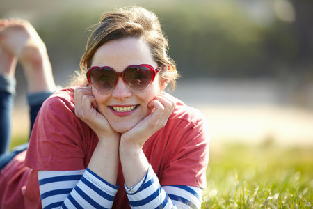 Portrait of young woman wearing heart shape sunglasses lying on grass