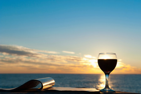 Glass of red wine with sea in background LANG_EVOIMAGES