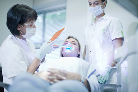 untruth: Dentist applying ultraviolet light to patients teeth LANG_EVOIMAGES