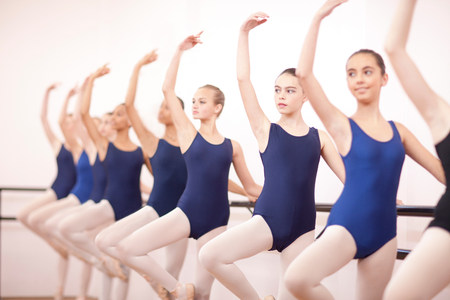Row of teenage ballerinas with arms outstretched LANG_EVOIMAGES