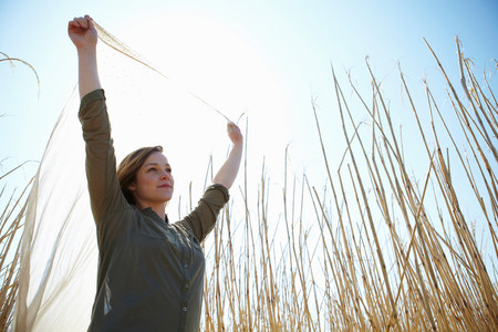 english ethnicity: Young woman holding up scarf in reeds