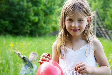 playground rides: Close portrait of young girl holding red balloon