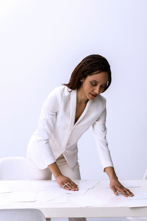 Young female arranging at paperwork on desk