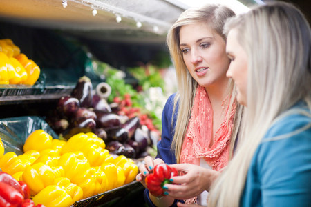 decide deciding: Young women looking at peppers in supermarket LANG_EVOIMAGES