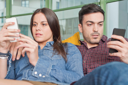 parlours: Young couple at home using mobile phones