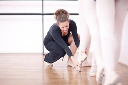 engrossed: Teacher adjusting teenage ballerinas feet pose
