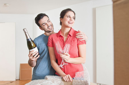 parlours: Young couple celebrating house move with champagne LANG_EVOIMAGES