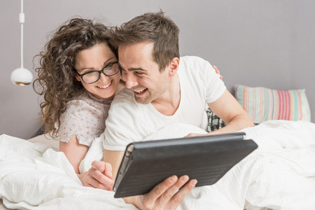 handheld device: Mid adult couple lying on bed using digital tablet