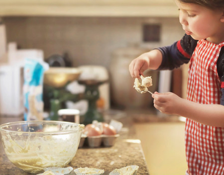 Child holding spoon with cake mix LANG_EVOIMAGES