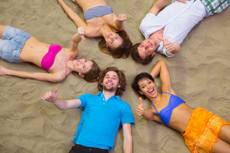 Aerial view of friends lying with heads together on sand
