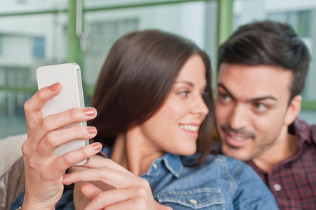 cropped out: Young couple at home looking at mobile phone