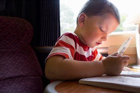 Close up of young boy with puzzle book on train LANG_EVOIMAGES