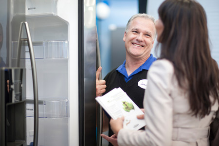 Salesman showing woman fridge in showroom