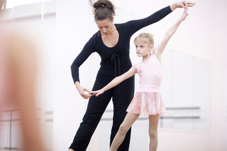 Young ballerina practicing pose with teacher LANG_EVOIMAGES