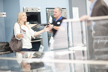 Young woman and salesman looking at ovens in showroom LANG_EVOIMAGES