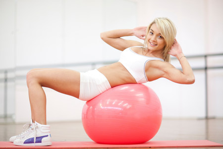 Young woman sitting on exercise ball in aerobics class