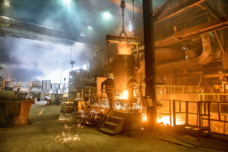 Steel workers watching furnace in steel foundry