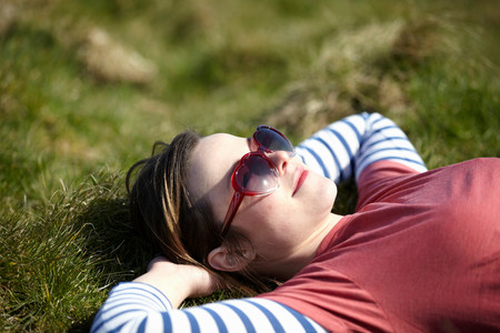 Young woman wearing heart shape sunglasses lying on grass LANG_EVOIMAGES