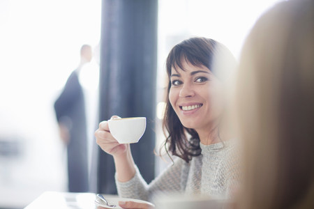 Mid adult woman in cafe with coffee