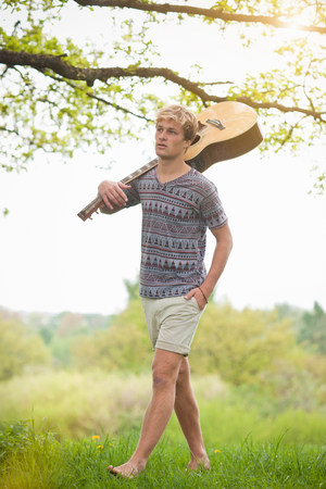 getting out: Young man walking through field with guitar