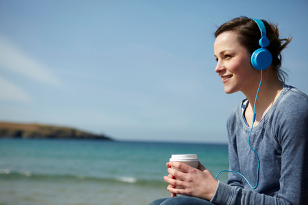 liberating: Young woman at coast with coffee and earphones