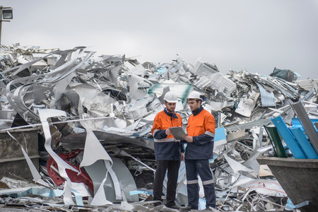 Two workers looking at clip board in front of scrap aluminum
