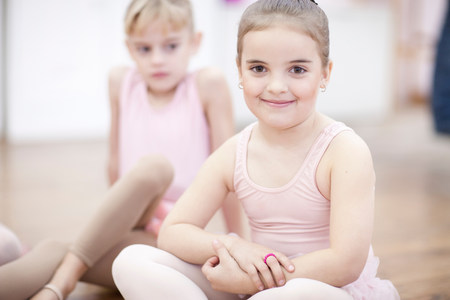 Two young ballerinas sitting on floor
